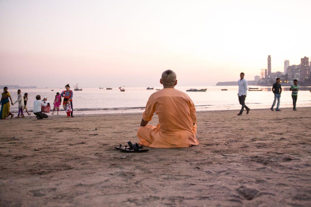 Prem Gauranga das sits for Gayatri as the sun sets over Chowpatty Beach. ©robertmoses